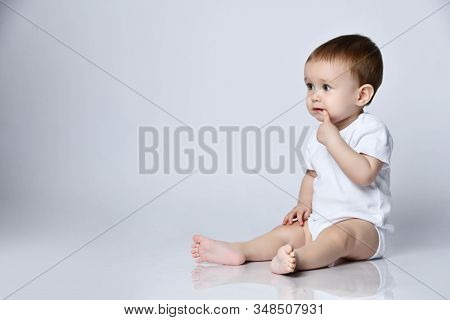 Calm Newborn Baby Boy Toddler Sitting Sideways On The Floor Looking Forward Holding Finger In His Mo