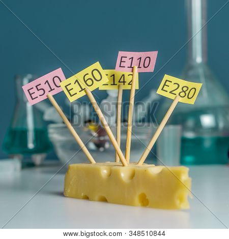 A Chees Decorated With Name Plates Of Additives E, Test Tubes Stand Nearby. Food Laboratory. Close U