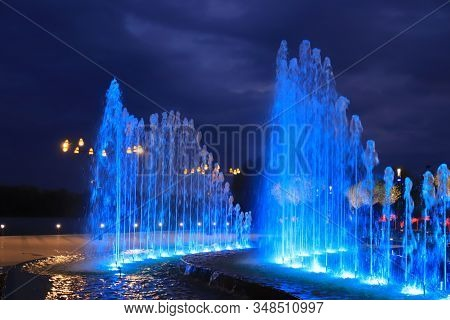 Beautiful Pool In The Landscape Park With A Fountain At Night Against The Backdrop Of Picturesque Cl