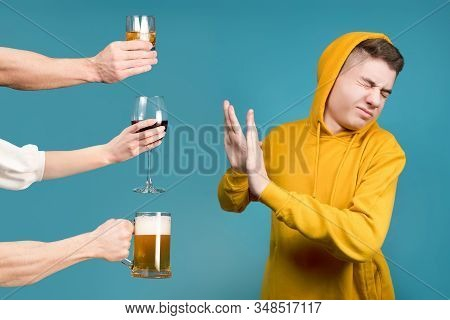 Teenager In A Yellow Sweatshirt Refuses Different Types Of Alcohol On A Blue Background
