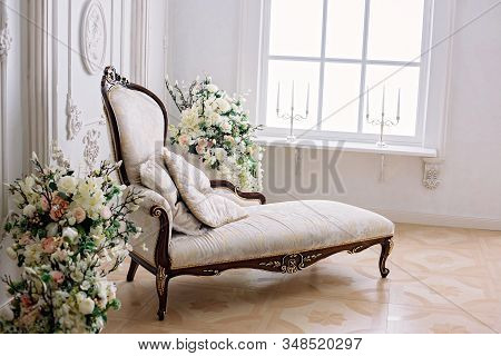 Rococo Style Sofa In A Bright Room Near A Vase Of Flowers And A Large Bright Window With Candlestick