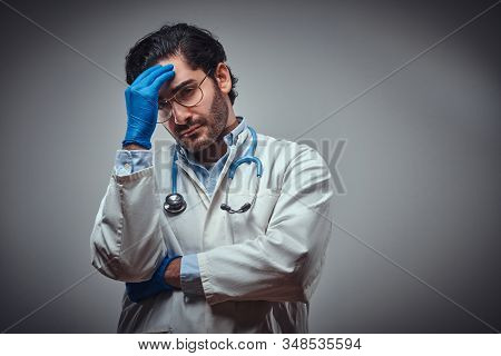 Attractive Doctor In Glasses And Protective Gloves Feels Tired After A Long Shift.