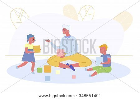 Granny Playing With Little Grandchildren Sitting On Floor Building Cubes Or Wooden Blocks Making Tow