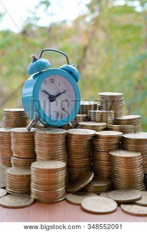 Blue Alarm Clock On Big Amount Of Shiny Ukrainian Old 1 Hryvnia Coin Stacks Close Up On Blurred Gree
