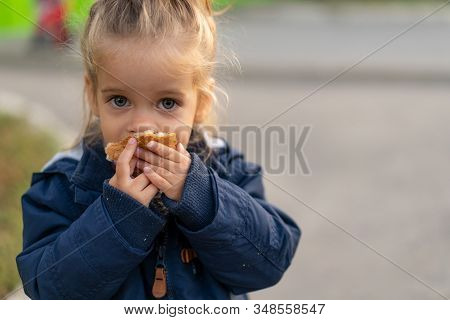 A Beautiful Little Caucasian Girl With Blond Hair And Eating Bread Eagerly With Her Hands Looks At T