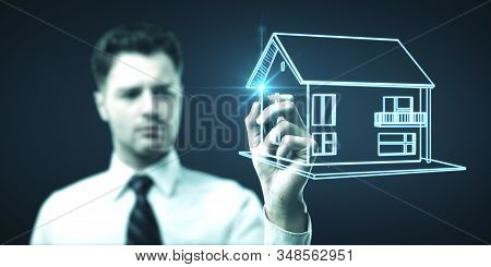 Businessman Drawing Glowing Cottage. Business And Building Concept.