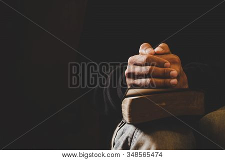 Soft Focus On A Hand Of Man While Praying For Christian Religion With Blurred Of Dark Background.
