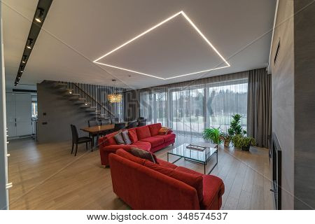 Main Living Area Of The Dwelling House With A Big Window, Furniture, Fireplace, Modern Lighting, Pot