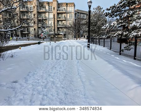 Edmonton, Alberta, Canada - March 18th, 2020: An Empty Sidewalk And Street With Old Footprints In Th