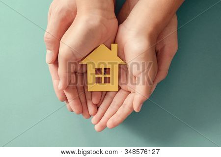 Hands Holding Yellow Paper House On Blue Background, Family Home, Homeless Shelter Housing And Home