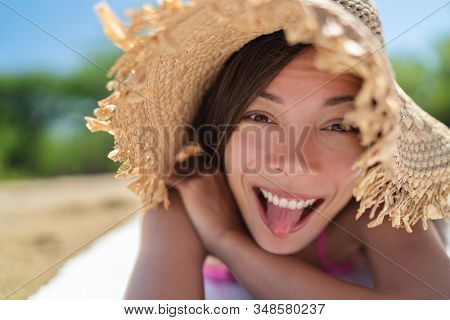 Happy funny face Asian young woman doing goofy facial expression sticking tongue out on summer vacation relax holiday sun tanning on beach having fun.