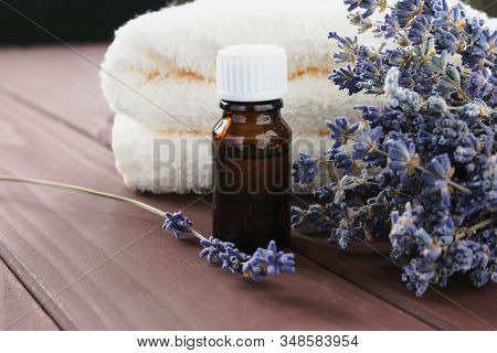 In A Dark Bottle, Essential Oil And A Bunch Of Dry Lavender Next To A White Terry Towel On A Brown B