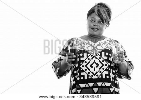 Happy Overweight African Woman Thinking While Holding Glass Of Soda Drink And Water