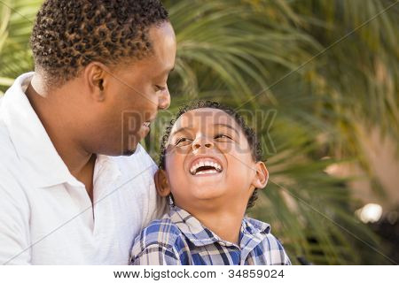 Happy Mixed Race Father and Son Playing in the Park.