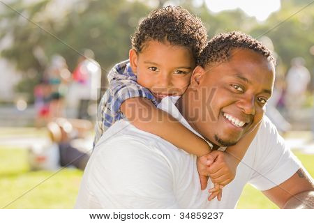 Happy African American Father and Mixed Race Son Playing Piggyback in the Park. poster
