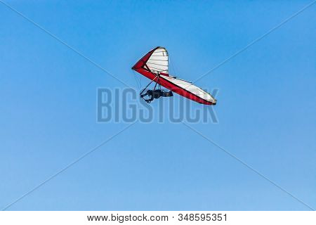 Overhead View Of Flying Hang-gliding Against The Clear Blue Sky. Hang Glider Flying Soaring On A Sun