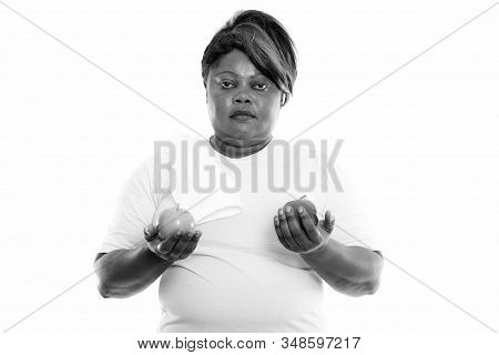Studio Shot Of Overweight African Woman Holding Two Apples Ready For Gym