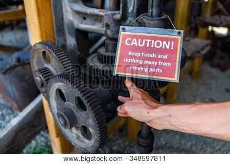 An Antique Industrial Engine With A Signboard - Caution, Keep Hands And Clothing Away From Moving Pa