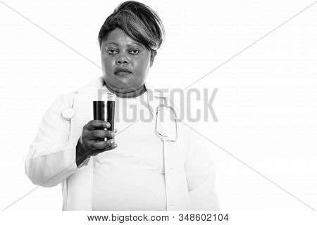Studio Shot Of Fat Black African Woman Doctor Holding Glass Of Soda Drink