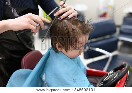 The Child Is Getting A Haircut At The Hairdresser In A Red Car. The First Haircut Of The Child In Th