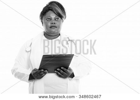 Studio Shot Of Fat Black African Woman Doctor Holding Clipboard While Thinking