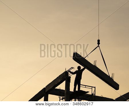Precast Concrete Beam Installed At Construction Site By Mobile Crane And Worker  ; Silhouette Pictur