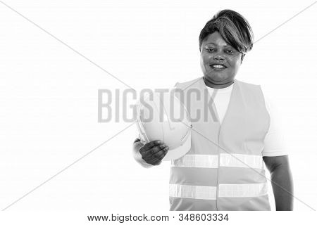 Studio Shot Of Happy Fat Black African Woman Construction Worker Smiling While Holding Hard Hat