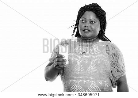 Studio Shot Of Fat Black African Woman Thinking While Holding Glass Of Milk