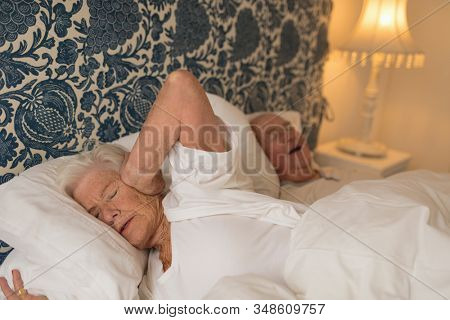 Senior woman covering ears while senior man snoring in bedroom at home