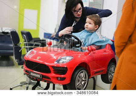 Hairdresser Haircuts A Child. The First Haircut Of The Child At The Hairdresser. Baby Haircut Toddle