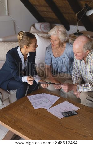 Front view of a female doctor and senior couple looking and discussing over clipboard they hold in their hands at home