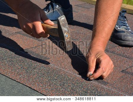 Roofing Contractor Laying Asphalt Shingles. House Roofing Construction With Roofing Shingles. Roofer