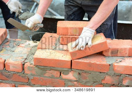 Bricklayer Hands In Masonry Gloves And Trowels Bricklaying House Wall. Building Contractors Bricklay