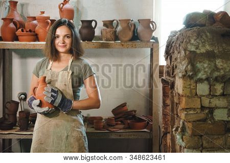 Young Woman Holds Clay Pots On Background Of Potteryproducts. Female Mastery Concept.