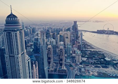 Aerial view of Dubai city. Drone fly over futuristic Dubai Marina district on beautiful sunset. Residential Modern skyscraper buildings, Jumeirah Beach, UAE, Middle East smart city