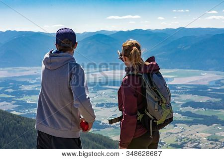Young Man And Woman Stand On The Hilltop And Talk About Their Route Direction. Kootenay Valley Mount