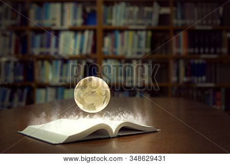 An Open Book Glows Brightly And Reveals A Globe Of The World, In Old Self Of Book Library University