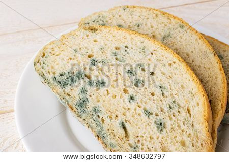 Close-up Of Stale Bread With Green Mildew On A White Saucer Over White Wooden Table. Spoiled Bread W