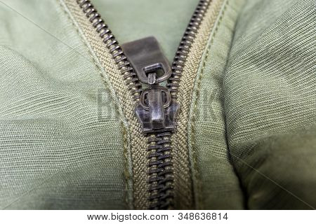 Fragment Of Partially Fastened Metal Zipper Fastener With Metal Puller On The Outerwear Olive Color