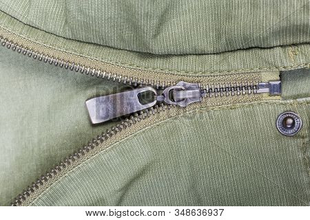Fragment Of Partially Fastened Metal Zipper Fastener With Metal Puller And Unbuttoned Snap Button Fa