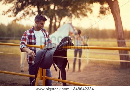 Man preparing a horse saddle for a ride,woman with a horse in the back. Training  on countryside, sunset golden hour. Freedom nature concept.