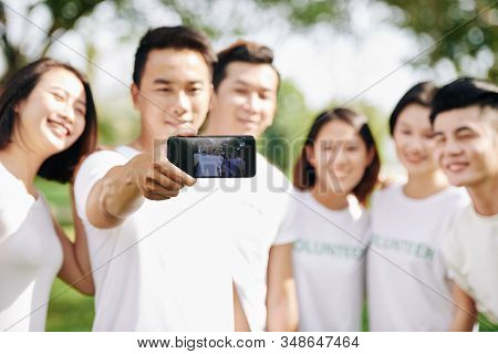 Young Smiling Volunteer Photograhing With Friends On Smartphone, Selective Focus