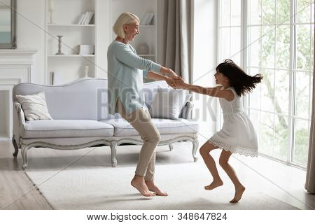 Energetic Grandmother Have Fun Dancing With Little Granddaughter
