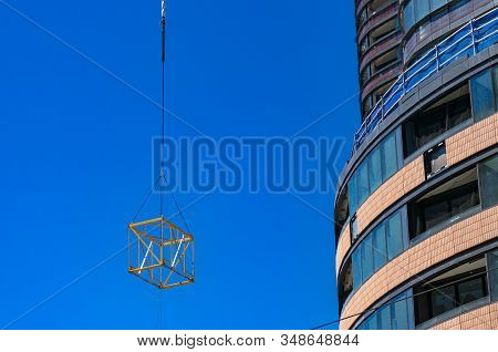Construction Site, Urban Development Background With Crane Lifting Cube Frame Structure. Highrise Bu