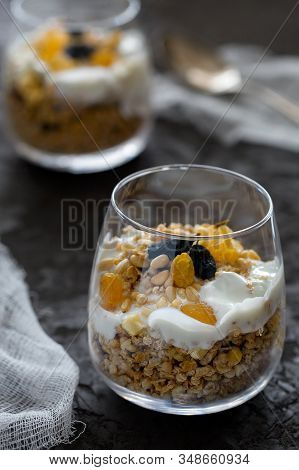 Homemade Organic Fresh Greek Yogurt Parfait With Granola,nuts And Raisins In Glass On Gray Concrete