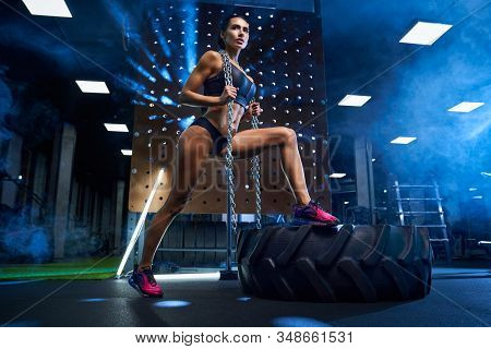 From Below View Of Fitness Woman In Black Sportswear With Raids Holding Chains On Neck. Athlete Fema