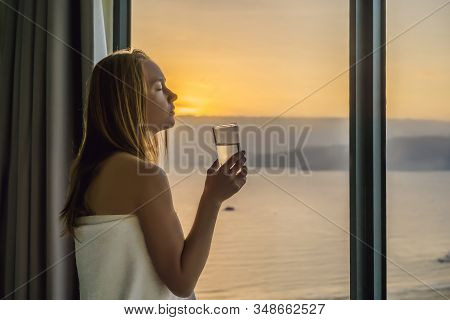 Woman Drinks Water In The Morning On A Background Of A Window With A Sea View