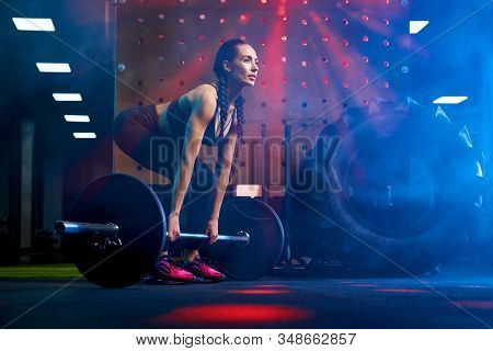 Side View Of Brunette Female Bodybuilder With Long Braids Doing Deadlift Using Barbell. Srtong Woman