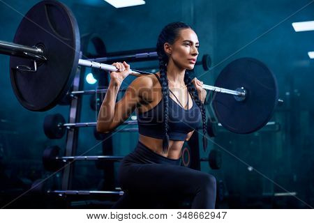 Side View Of Brunette Female Bodybuilder With Long Braids Doing Squats, Holding Barbell On Shoulders