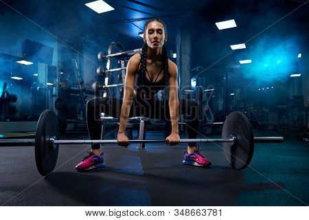 Front View Of Female Bodybuilder With Braids Touching Barbell On Floor. Srtong Woman With Muscular B